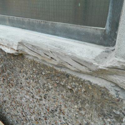 Betonfensterbank mit abgeplatzten Stellen