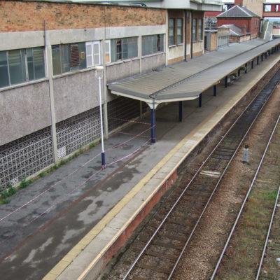 Betonwand mit starken Schäden durch Abplatzungen an einem Bahnhof